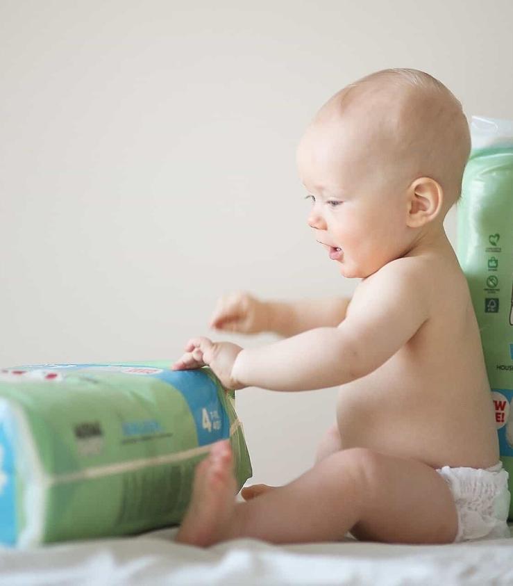 Muumibaby vauva istuu vaippapakkausten kanssa